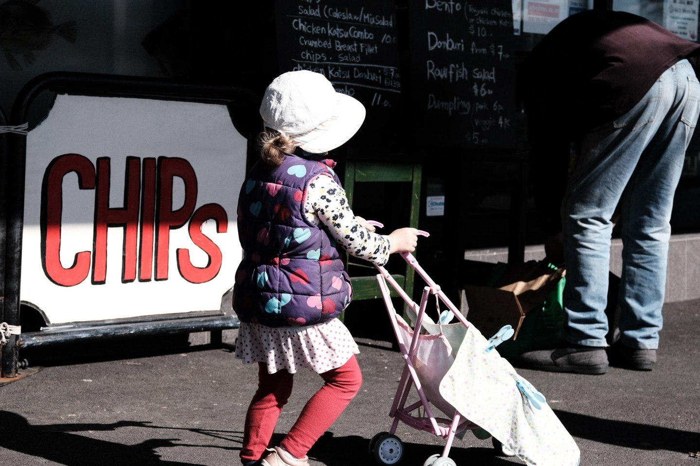 Little girl walking past a fish chips shop